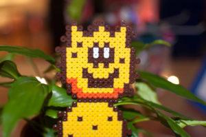 Foto eines Pokey Stachel Monsters von Nintendo aus Bügelperlen gemacht, mit Pflanze im Hintergrund