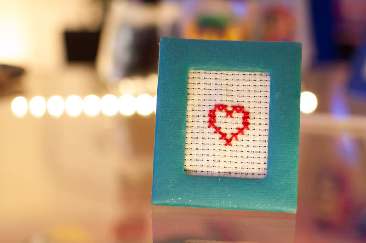 Ein ganz einfach gehaltener Liebesbeweis für alle Verliebten, Verheirateten oder als Geschenk zur Hochzeit, Valentinstag oder auch Muttertag: ein rot gesticktes Herz in einem blau glitzernden Rahmen. Schnörkellos und dennoch ein bisschen kitschig.