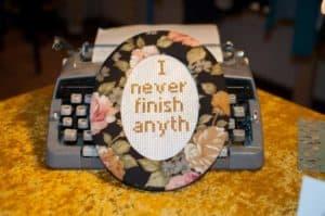 """""""I never finish anyth"""" Stickbild im Rahmen von Oma. Im Hintergrund ist eine alte Schreibmaschine zu sehen"""